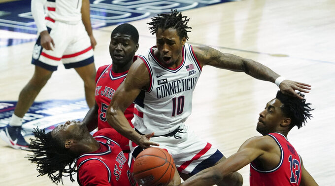 UConn guard Brendan Adams (10) fouls St. John's guard Posh Alexander, left foreground, in the first half of an NCAA college basketball game in Storrs, Connecticut, Monday, Jan. 18, 2021.  (David Butler II/Pool photo via AP)