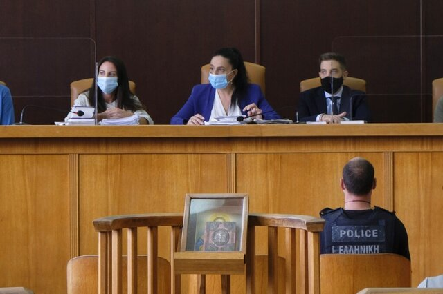 Yiannis Paraskakis, bottom right, who accused of the brutal killing of American biologist Suzanne Eaton in 2019, wearing a bulletproof vest that reads