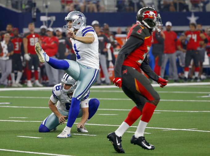 Dallas Cowboys' Kasey Redfern (1) attempts an extra point as punter Chris Jones (6) watches that bounced off the upright and landed in the end zone for no score in the first half of a preseason NFL football game against the Tampa Bay Buccaneers in Arlington, Texas, Thursday, Aug. 29, 2019. (AP Photo/Ron Jenkins)