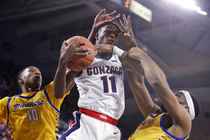 Gonzaga guard Joel Ayayi, center, grabs a rebound between Cal State Bakersfield guard Justin Edler-Davis, left, and forward Darrin Person Jr. during the first half of an NCAA college basketball game in Spokane, Wash., Saturday, Nov. 23, 2019. (AP Photo/Young Kwak)