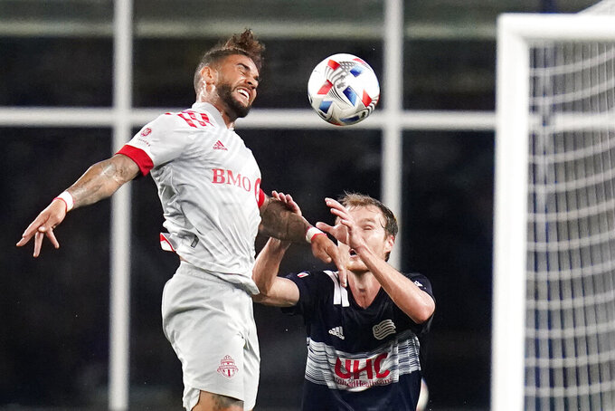 Toronto FC forward Dom Dwyer, left, heads the ball against New England Revolution defender Henry Kessler, right, during the second half of an MLS soccer match, Wednesday, July 7, 2021, in Foxborough, Mass. Toronto won 3-2. (AP Photo/Charles Krupa)