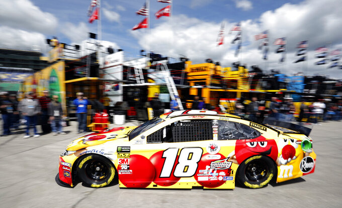Driver Kyle Busch (18) pulls out of the garage area to practice for a NASCAR Cup Series auto race at Kansas Speedway in Kansas City, Kan., Friday, May 10, 2019. (AP Photo/Colin E. Braley)