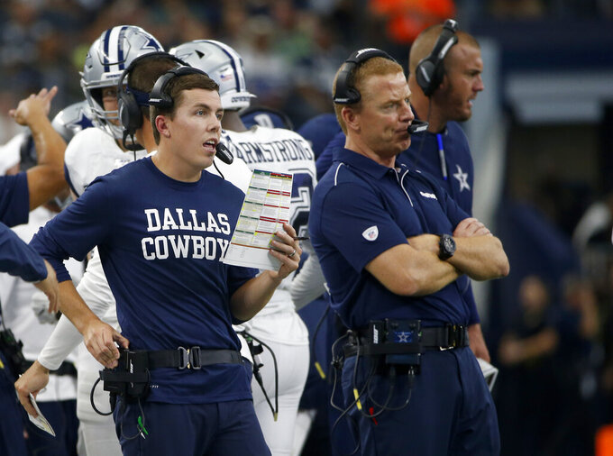 Dallas Cowboys offensive coordinator Kellen Moore, left, makes a call as head coach Jason Garrett, right, stands by in the first half of an NFL football game against the Miami Dolphins in Arlington, Texas, Sunday, Sept. 22, 2019. (AP Photo/Ron Jenkins)