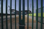 FILE - In this April 9, 2020, file photo, Gates stand locked outside the closed Manchester City Etihad Stadium, in Manchester, northern England, as the English Premier League soccer season has been suspended due to coronavirus. With no games being played, recent sports headlines have centered around hopes and dreams — namely, the uncharted path leagues and teams must navigate to return to competition in the wake of the pandemic. (AP Photo/Jon Super, File)