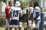 Los Angeles Chargers quarterback Philip Rivers, left, wide receiver Keenan Allen, and defensive end Melvin Ingram, right, chat with New Orleans Saints wide receiver Ted Ginn during a joint NFL practice in Costa Mesa, Calif., Thursday, Aug. 15, 2019. (AP Photo/Kyusung Gong)