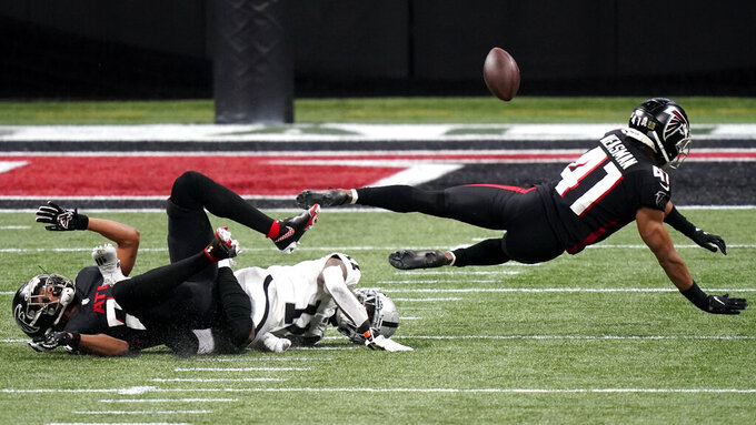 Las Vegas Raiders wide receiver Henry Ruggs III (11) is hit by Atlanta Falcons safety Sharrod Neasman (41) during the first half of an NFL football game, Sunday, Nov. 29, 2020, in Atlanta. (AP Photo/Brynn Anderson)