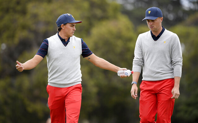 U.S. team player Rickie Fowler, left, and playing partner Justin Thomas talk while walking on the 6th fairway in their foursome match during the President's Cup golf tournament at Royal Melbourne Golf Club in Melbourne, Saturday, Dec. 14, 2019. (AP Photo/Andy Brownbill)