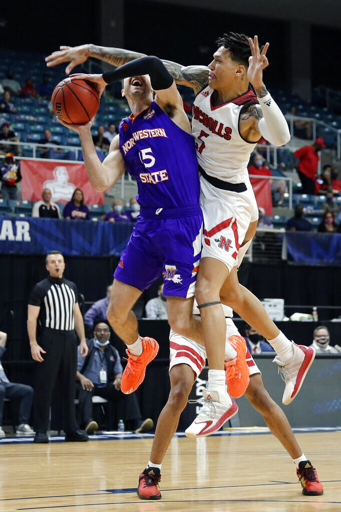 Nicholls State forward Najee Garvin (5) blocks the shot attempt by Northwestern State guard Jovan Zelenbaba (15) during the second half of an NCAA college basketball game in the Southland Conference men's touranment semifinals Friday, March 12, 2021, in Katy, Texas. (AP Photo/Michael Wyke)