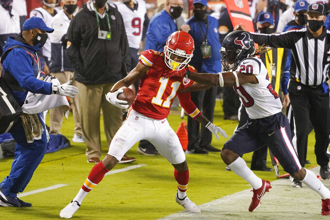 Kansas City Chiefs wide receiver Demarcus Robinson (11) is pushed out of bounds by Houston Texans safety Justin Reid (20) in the first half of an NFL football game Thursday, Sept. 10, 2020, in Kansas City, Mo. (AP Photo/Charlie Riedel)