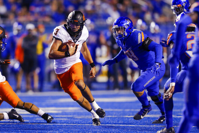 Oklahoma State quarterback Spencer Sanders (3) runs with the ball past Boise State defensive end Demitri Washington (38) during the first half of an NCAA college football game Saturday, Sept. 18, 2021, in Boise, Idaho. (AP Photo/Steve Conner)