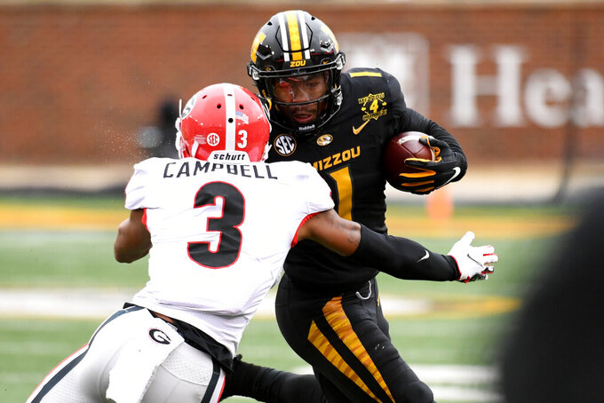 Missouri running back Tyler Badie, right, runs with the ball as Georgia defensive back Tyson Campbell (3) defends during the second half of an NCAA college football game Saturday, Dec. 12, 2020, in Columbia, Mo. (AP Photo/L.G. Patterson)