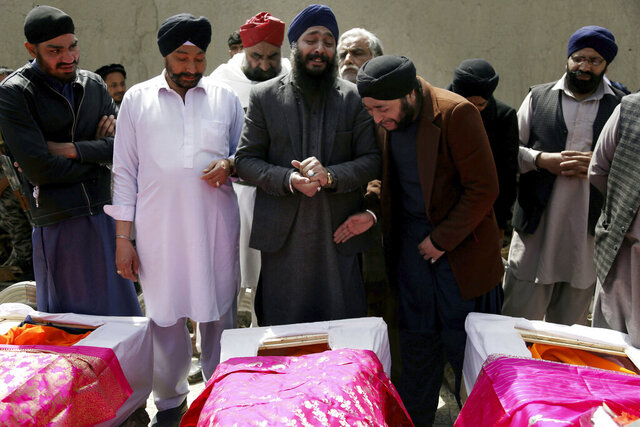 FILE- in this Thursday, March 26, 2020 file photo, Afghan Sikh men mourn their beloved ones during a funeral procession for those who were killed on Wednesday by a lone Islamic State gunman, rampaged through a Sikh house of worship, in Kabul, Afghanistan. Afghanistan's dwindling community of Sikhs and Hindus is shrinking to its lowest levels. With growing threats from the local Islamic State affiliate, many are choosing to leave the country of their birth to escape the insecurity and a once-thriving community of as many as 250,000 members now counts fewer than 700.  (AP Photo/Tamana Sarwary, File)