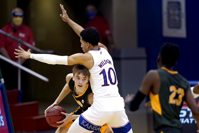 North Dakota State's Grant Nelson looks to pass under pressure from Kansas' Jalen Wilson (10) during the second half of an NCAA college basketball game Saturday, Dec. 5, 2020, in Lawrence, Kan.  (AP Photo/Charlie Riedel)