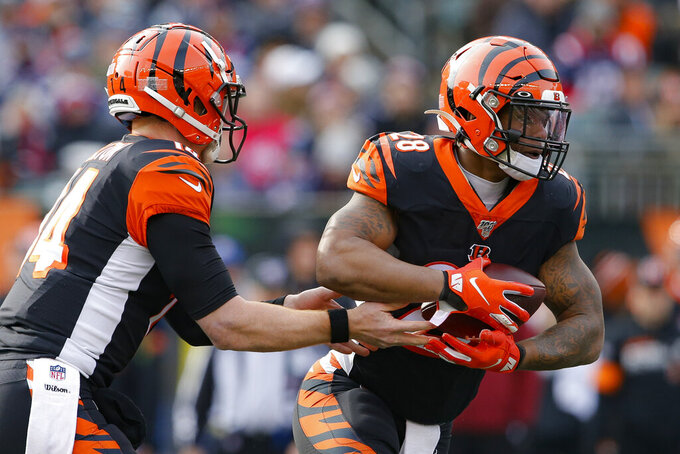 Cincinnati Bengals quarterback Andy Dalton, left, hands off the ball to running back Joe Mixon (28) in the first half of an NFL football game against the New England Patriots, Sunday, Dec. 15, 2019, in Cincinnati. (AP Photo/Gary Landers)