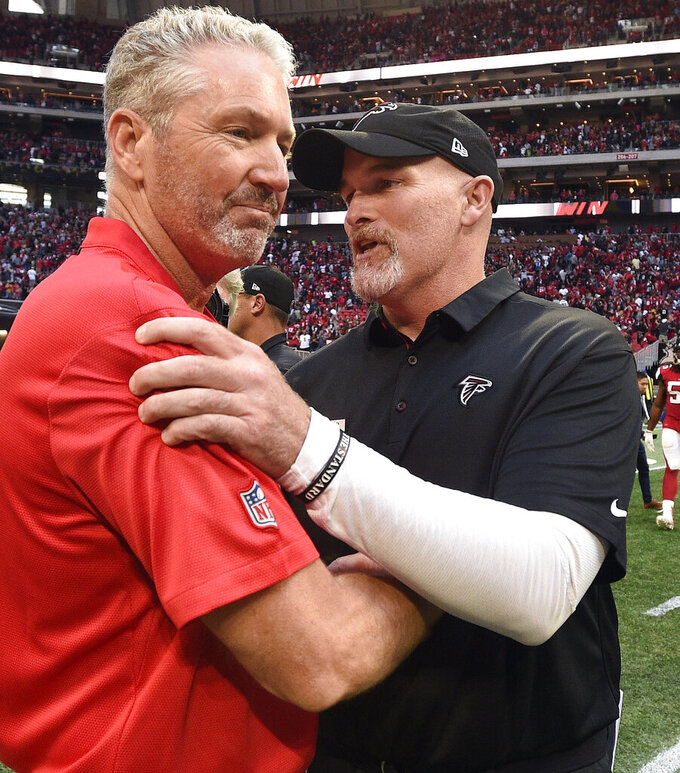 FILE - In this Oct. 14, 2018, file photo, then-Tampa Bay Buccaneers head coach Dirk Koetter, left, speaks with Atlanta Falcons head coach Dan Quinn after an NFL football game, in Atlanta. Falcons coach Quinn says the team's outside zone scheme won't change with newly hired offensive coordinator Dirk Koetter.  (AP Photo/John Amis, File)