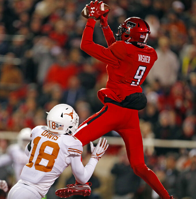 Texas Tech's T.J. Vasher (9) catches a touchdown pass over Texas Davante Davis during the first half of an NCAA college football game Saturday, Nov. 10, 2018, in Lubbock, Texas. (AP Photo/Brad Tollefson)