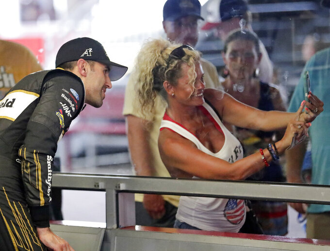 Aric Almirola, left, poses for a selfie photo in his garage with a fan during practice for the NASCAR Cup Series auto race at Daytona International Speedway, Thursday, July 4, 2019, in Daytona Beach, Fla. (AP Photo/John Raoux)