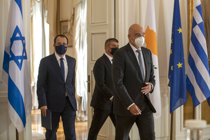 Foreign Ministers of Greece Nikos Dendias, front Israel Gabi Ashkenazi , and Cyprus Nikos Christodoulides, left, arrive for a news conference after their meeting in Athens, on Tuesday, Oct. 27, 2020. (AP Photo/Petros Giannakouris)