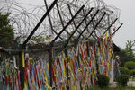 A man wearing a face mask walks near the wire fences decorated with ribbons written with messages wishing for the reunification of the two Koreas at the Imjingak Pavilion in Paju, South Korea, Thursday, June 18, 2020. Relations between the Koreas have been strained since a second Kim-Trump summit in early 2019 fell apart due to wrangling over the sanctions. (AP Photo/Lee Jin-man)