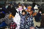 Two girls from Afghanistan wait with other evacuees to fly to the United States or another safe location in a makeshift gate inside a hanger at the U.S. Air Base in Ramstein, Germany, Wednesday, Sept. 1, 2021. The United States is using the military base in Ramstein, Palatinate, as a hub for the evacuation of shelter seekers and local forces from Afghanistan. (AP Photo/Markus Schreiber)