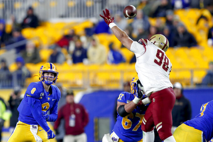 Pittsburgh quarterback Kenny Pickett (8) gets a pass over Boston College defensive tackle Kyiev Bennermon (98) during the second half of an NCAA college football game, Saturday, Nov. 30, 2019, in Pittsburgh. (AP Photo/Keith Srakocic)