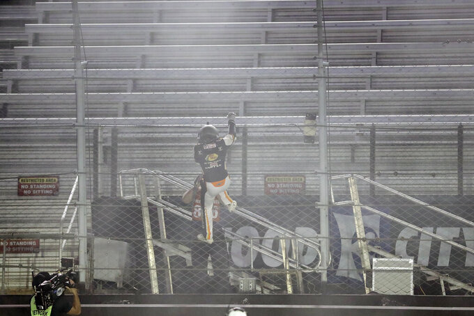 Noah Gragson (9) celebrates by climbing the fence in front of empty stands after winning a NASCAR Xfinity Series auto race at Bristol Motor Speedway Monday, June 1, 2020, in Bristol, Tenn. (AP Photo/Mark Humphrey)