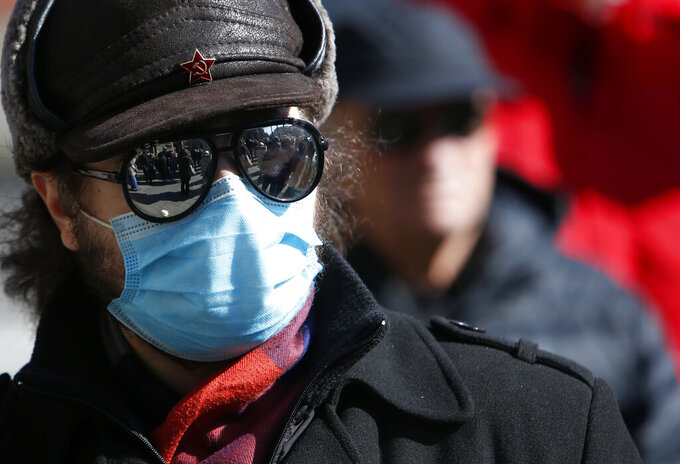 A man wearing a face mask to protect against coronavirus attends during protest in front of the government building in Belgrade, Serbia, Monday, Feb. 15, 2021. Hundreds gathered outside the government headquarters to honor dozens of medical staff who died since the start of the outbreak. (AP Photo/Darko Vojinovic)
