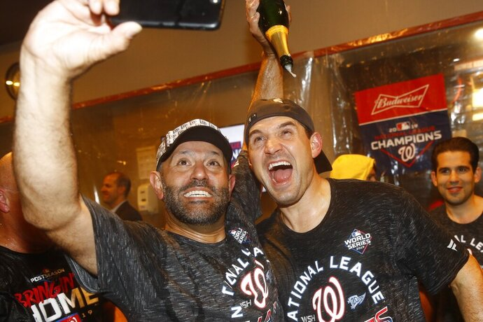 Washington Nationals' Ryan Zimmerman and Dr. Hirad Bagy celebrate after Game 4 of the baseball National League Championship Series against the St. Louis Cardinals Wednesday, Oct. 16, 2019, in Washington. The Nationals won 7-4 to win the series 4-0. (AP Photo/Patrick Semansky)