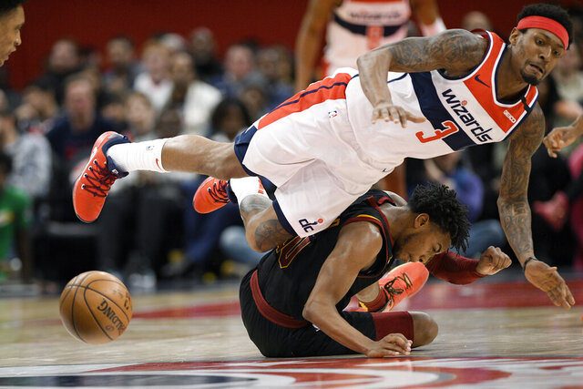 Cleveland Cavaliers guard Darius Garland, bottom, and Washington Wizards guard Bradley Beal are unable to come up with the ball during the second half of an NBA basketball game Friday, Feb. 21, 2020, in Washington. Garland was called for a foul on the play. The Cavaliers won 113-108. (AP Photo/Nick Wass)