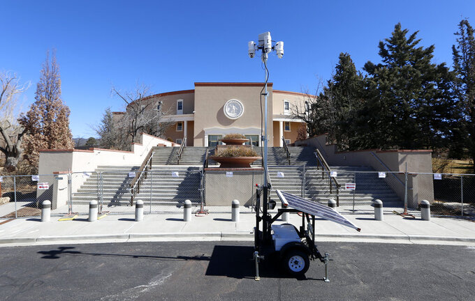 """A fence is seen surrounding the State Capitol in Santa Fe, on Wednesday, Feb. 24, 2021. Republican lawmakers in New Mexico have asked that the state remove protective barriers erected around the state Capitol following the Jan. 6 insurrection in which supporters of former President Donald Trump broke into the U.S. Capitol building in an attempt to overturn the results of the presidential election. Republicans in the state legislature asked the Legislative Council on Tuesday to remove the fences around the facility, arguing that """"the threat has not materialized."""" (Luis Sánchez Saturno/The New Mexican via AP)"""