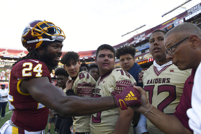 Washington Redskins cornerback Josh Norman (24) greets fans along the sideline before the team's NFL preseason football game against the Cincinnati Bengals in Landover, Md., Thursday, Aug. 15, 2019. (AP Photo/Susan Walsh)
