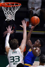 Pittsburgh guard Xavier Johnson (1) takes a shot against Miami forward Matt Cross (33) during the first half of an NCAA college basketball game, Wednesday, Dec. 16, 2020, in Coral Gables, Fla. (AP Photo/Wilfredo Lee)