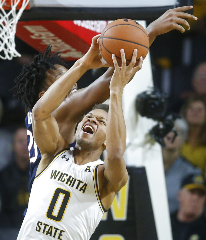 Wichita State guard Dexter Dennis fights for a rebound against Connecticut forward Josh Carlton during the first half of an NCAA college basketball game in Wichita, Kan., Thursday, Feb. 28, 2019. (Travis Heying/The Wichita Eagle via AP)