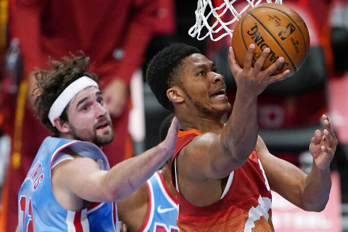 Denver Nuggets guard PJ Dozier shoots next to Brooklyn Nets forward Joe Harris during the first quarter of an NBA basketball game, Tuesday, Jan. 12, 2021, in New York. (AP Photo/Kathy Willens)