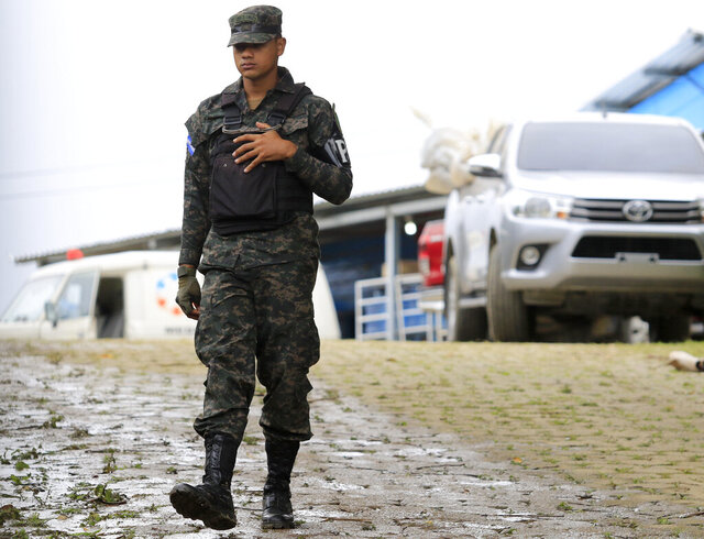 A military police officer walks past a pick-up truck loaded with the bodies of dead inmates that is parked in the Tela prison where at least 18 prisoners were killed during an prisoner's riot on Friday in Tela, Honduras, Saturday, Dec. 21, 2019. The riot came several days after Honduras declared a state of emergency in its prison system. (AP Photo/Delmer Martinez)