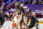 Minnesota's Marcus Carr (5) drives around Maryland's Darryl Morsell (11) and Galin Smith (30) in the first half of an NCAA college basketball game, Saturday, Jan. 23, 2021, in Minneapolis. (AP Photo/Jim Mone)