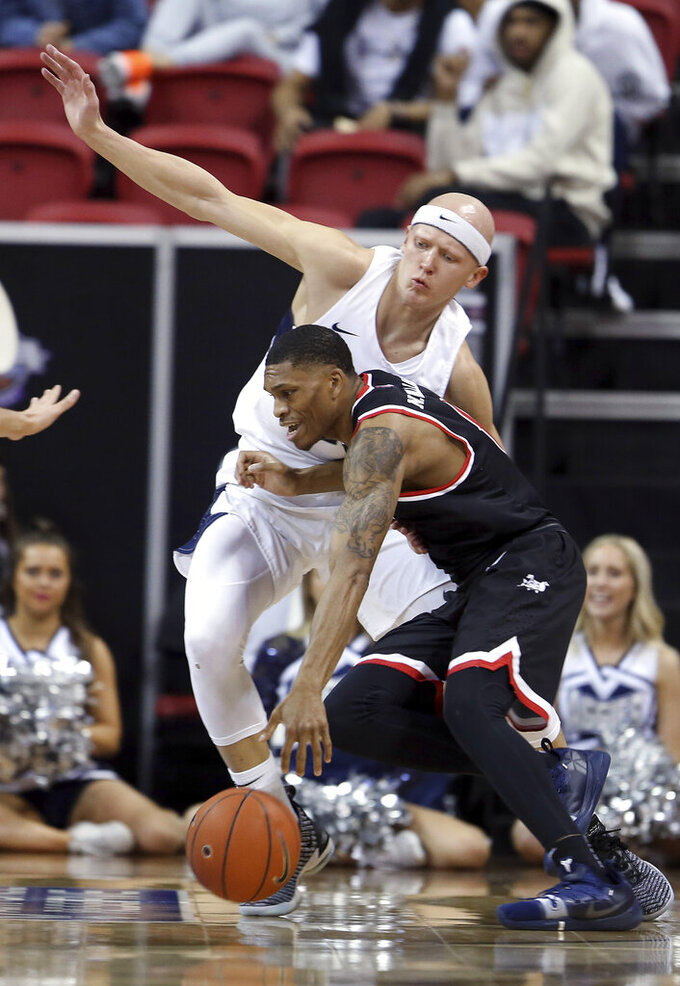 Utah State's Brock Miller defends as Fresno State's New Williams drives during the first half of an NCAA college basketball game in the Mountain West Conference men's tournament Friday, March 15, 2019, in Las Vegas. (AP Photo/Isaac Brekken)