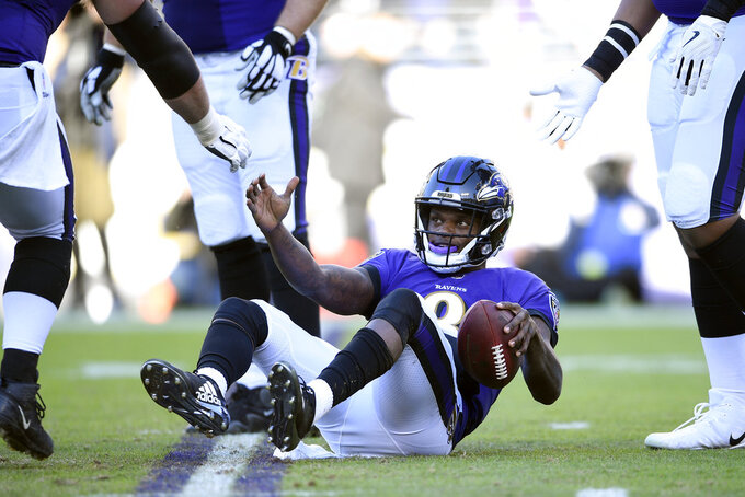 Teammates help Baltimore Ravens quarterback Lamar Jackson to his feet after a play in the second half of an NFL wild card playoff football game against the Los Angeles Chargers, Sunday, Jan. 6, 2019, in Baltimore. (AP Photo/Nick Wass)