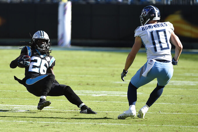 Carolina Panthers cornerback Donte Jackson (26) slides following an interception while Tennessee Titans wide receiver Adam Humphries (10) looks to tackle during the first half of an NFL football game in Charlotte, N.C., Sunday, Nov. 3, 2019. (AP Photo/Mike McCarn)