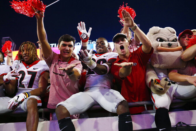 "Georgia defensive back J.R. Reed (20) does the ""gator chop"" with fans in celebration after after the team's win over Florida in an NCAA college football game Saturday, Nov. 2, 2019, in Jacksonville, Fla. (Joshua L. Jones/Athens Banner-Herald via AP)"