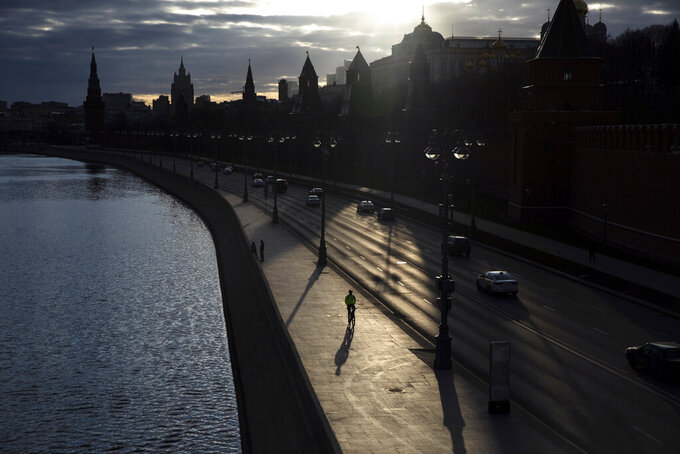In this April 10, 2020, photo, a man rides a bike along the embankment of the Moskva River in front of the Kremlin in Moscow, Russia. As countries across the world seek to get their economies back on track after coronavirus lockdowns are over, some people are encouraging the use of bicycles as a way to avoid unsafe crowding on trains and buses. (AP Photo/Pavel Golovkin)