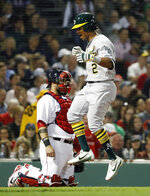 Oakland Athletics' Khris Davis hits home plate as Boston Red Sox catcher Sandy Leon looks on after hitting a home run during the eighth inning of a baseball game at Fenway Park in Boston Monday, May 14, 2018. (AP Photo/Winslow Townson)