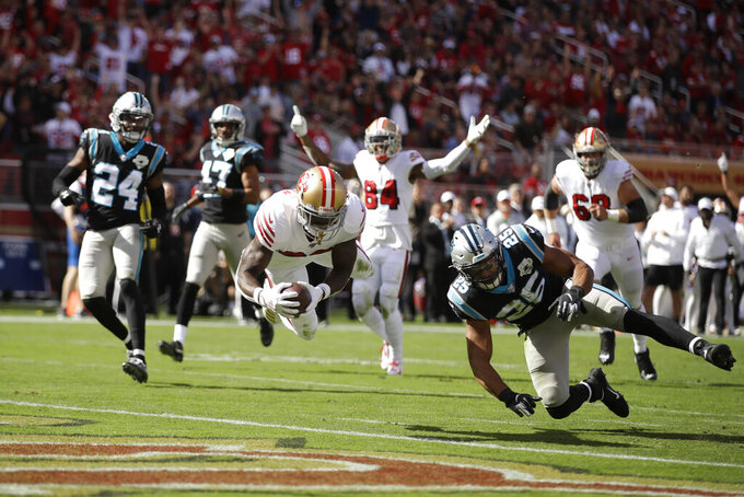 San Francisco 49ers running back Tevin Coleman goes diving into the end zone to score a touchdown as Carolina Panthers strong safety Eric Reid (25) and cornerback James Bradberry (24) look on during the first half of an NFL football game in Santa Clara, Calif., Sunday, Oct. 27, 2019. In the background is San Francisco 49ers wide receiver Kendrick Bourne (84). (AP Photo/Ben Margot)