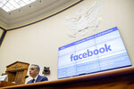 A list of settlements, violations and breaches scrolls over Facebook's logo on a screen behind David Marcus, CEO of Facebook's Calibra digital wallet service, left, as he speaks during a House Financial Services Committee hearing on Facebook's proposed cryptocurrency on Capitol Hill in Washington, Wednesday, July 17, 2019. (AP Photo/Andrew Harnik)