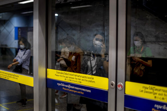 Commuters wearing face masks are mirrored in a subway station Bangkok, Thailand, Wednesday, Feb. 19, 2020. Thai Public Health Ministry on Monday, Feb 17, 2020 advised Thai travelers to reschedule their visits to Japan and Singapore citing the rising number of people infected by new coronavirus in those two countries. (AP Photo/Gemunu Amarasinghe)