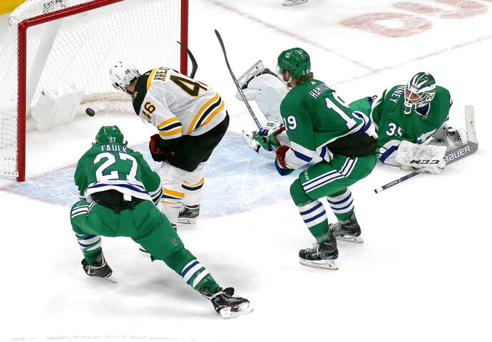 Boston Bruins center David Krejci (46) scores the game-winning goal past Carolina Hurricanes goaltender Curtis McElhinney (35) and defenders Justin Faulk (27) and Dougie Hamilton (19) during extra time of an NHL hockey game, Tuesday, March 5, 2019, in Boston. (AP Photo/Mary Schwalm)