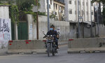 A Palestinian man rides his motorcycle on a road next to barriers set up during a lockdown imposed following the discovery of a rise in coronavirus cases in Gaza City , Monday, Aug. 31, 2020. (AP Photo/Hatem Moussa)