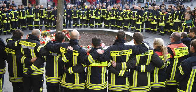 Firemen mourn at Königsplatz in Augsburg, German, Sunday, Dec.8, 2019. On the evening of Dec. 6 a fireman was so badly injured in his spare time here in an argument with a group that he died. (Stefan Puchner/dpa via AP)
