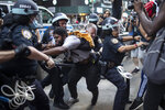 Police detain protesters as they march down the street during a solidarity rally for George Floyd, Saturday, May 30, 2020, in New York. Protests were held throughout the city over the death of George Floyd, a black man who died after being restrained by Minneapolis police officers on May 25. (AP Photo/Wong Maye-E)