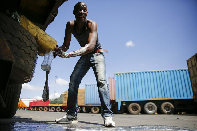 In this photo taken Monday, June 1, 2020, Tanzanian truck driver Ally Akida Samwel washes his hands next to his truck as he waits to be allowed to enter on the Kenya side of the Namanga border crossing with Tanzania. Africa's long-haul truckers carry food, fuel and other essential supplies along dangerous roads, but now they say they are increasingly accused of carrying the coronavirus as well. The drivers say they are stigmatized and even threatened in some countries. (AP Photo/Brian Inganga)